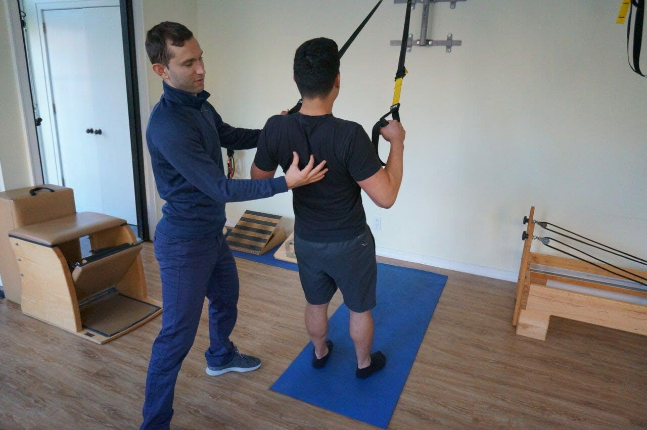 Igor Kozlov, DPT treating patient using TRX for back exercise