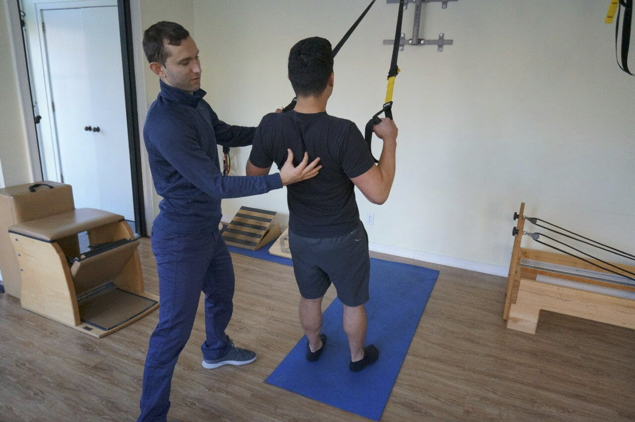 Igor Kozlov, DPT treating patient using TRX for back exercise