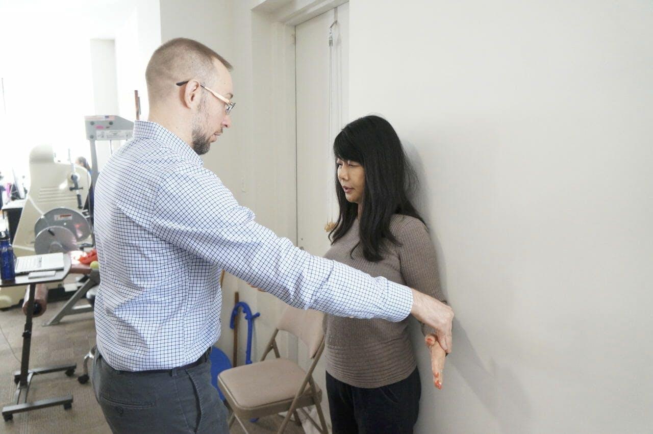 Edward Umheiser, DPT teaching the patient shoulder exercises.