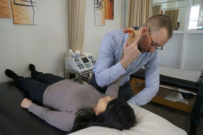 Edward Umheiser, DPT helping patient mobilize shoulder