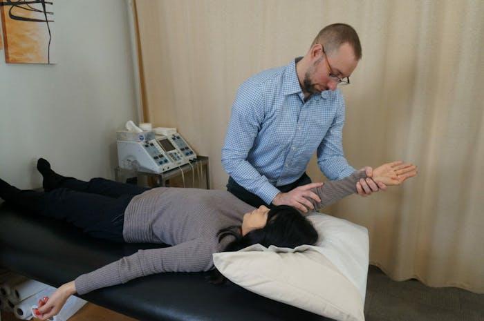 Edward Umheiser, DPT stretching patient's shoulder