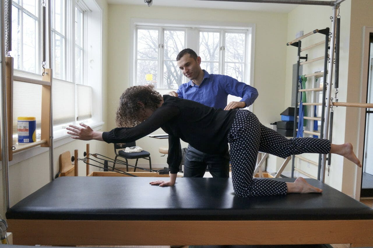 Igor assisting his patient with a spine stabilization exercise.