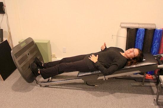 woman doing exercises on squat machine