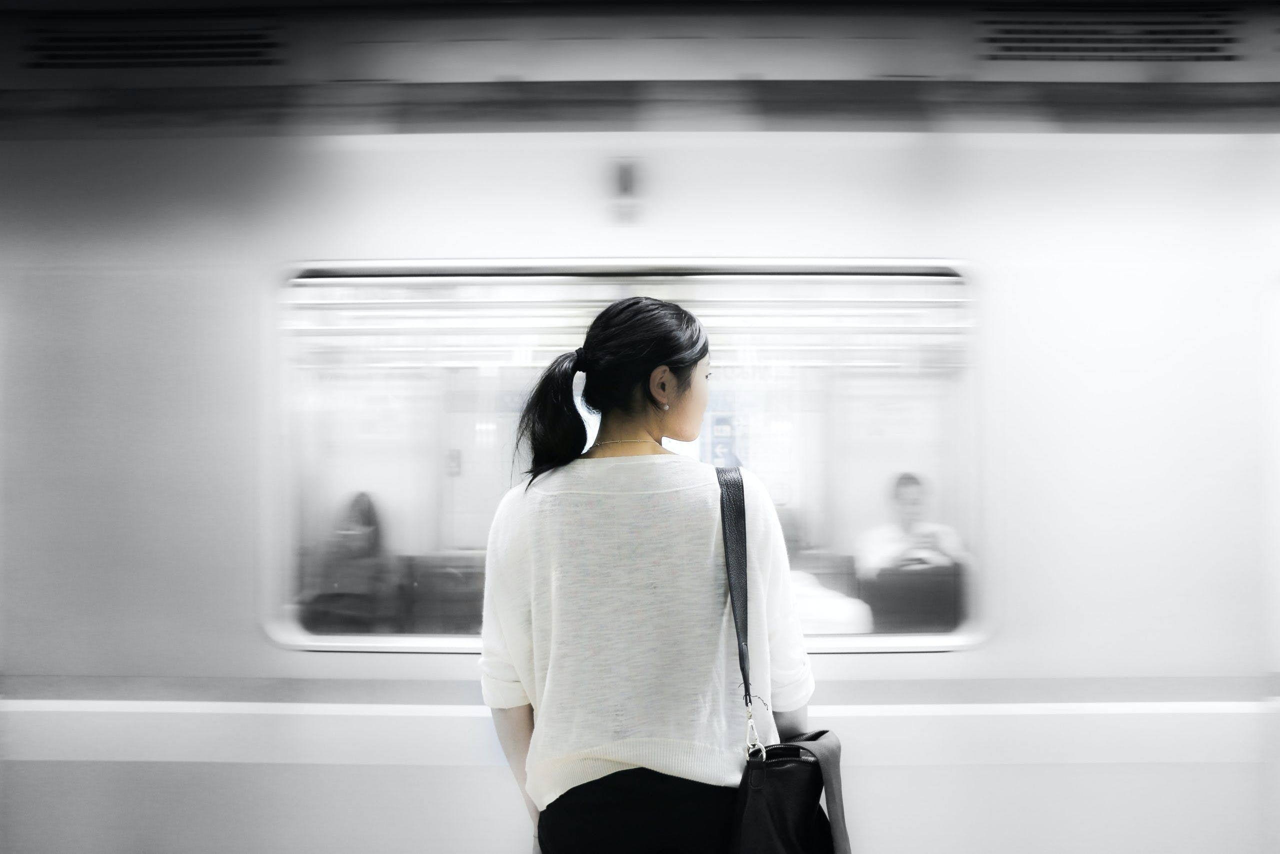 young woman standing alone in front of subway